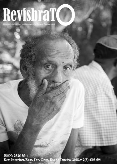 Fotografia em preto e branco com um homem negro idoso usando camiseta branca sentado e passando a sua mão direita na boca e olhando fixamente para a câmera. Ao fundo um outro homem negro sentado e de costas para a câmera, careca e usando boné.